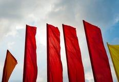 Flaggor på vinden på bakgrund för deppighethimmel Arkivfoton