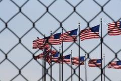 Flaggor till och med en staketsymbolism arkivfoto