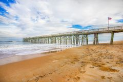 Flagler Beach With Pier And American Flag. The Flagler Beach, with the municipal pier, boardwalk and an American flag on it Royalty Free Stock Photo