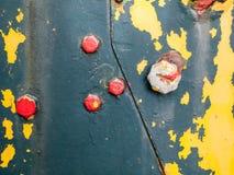 Flagnande målarfärg på rostigt järn med bultar Fotografering för Bildbyråer