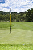 Flagpole, Ball, Green & Fairway. In the foreground are the ball & the green. Flagpole, is positioned in the middle of the green, behind that the fairway approach Stock Photos