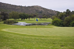 Flagpole, Green & Water Hazard. In the foreground is the rough fringe the surrounds the green Royalty Free Stock Photography