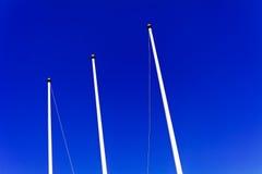 Flagpoles against blue sky Royalty Free Stock Photos
