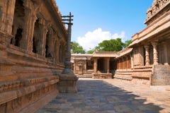 Flagpost och 100 pelare Maha-mandapa, Airavatesvara tempel, Darasuram, Tamil Nadu Den Nataraja mandapaen ses på slutet Sikt från Royaltyfria Bilder