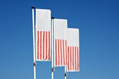 Flags. Three flags, blowing in the wind, with a beautiful blue sky in the background Royalty Free Stock Images