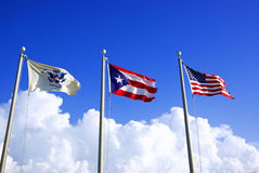 Flags. Of puerto rico and united states over blue cloudy sky Royalty Free Stock Images