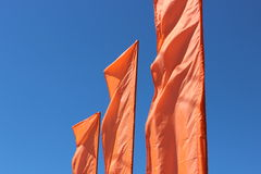 Flags. Orange flags against the blue sky Royalty Free Stock Image