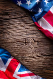 Flags of american and united kingdom on rustic oak board. UK and USA flags together diagonally stock photo