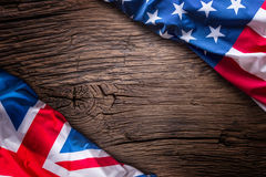 Flags of american and united kingdom on rustic oak board. UK and USA flags together diagonally stock photos