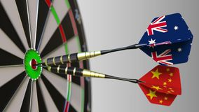 Flags of Australia and China on darts hitting bullseye of the target. International cooperation or competition. Animation stock video footage