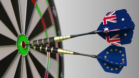 Flags of Australia and the European Union on darts hitting bullseye of the target. International cooperation or. Competition animation stock footage