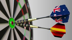 Flags of Australia and Germany on darts hitting bullseye of the target. International cooperation or competition. Animation stock footage