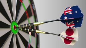 Flags of Australia and Japan on darts hitting bullseye of the target. International cooperation or competition. Animation stock footage