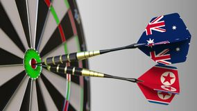 Flags of Australia and North Korea on darts hitting bullseye of the target. International cooperation or competition. Animation stock video footage