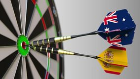 Flags of Australia and Spain on darts hitting bullseye of the target. International cooperation or competition. Animation stock footage