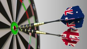 Flags of Australia and the United Kingdom on darts hitting bullseye of the target. International cooperation or. Competition animation stock video footage