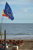 Flags at the beach with sunbeds Stock Photo