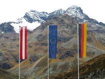 Flags of border area in alpine landscape. Three flags at a border area: the Flag of Austria, the Flag of Europe and the Flag of Germany - in front of a towering Royalty Free Stock Photography