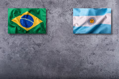 Flags of the Brazil and the Argentina on concrete background Royalty Free Stock Photos
