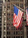 Flags and Brownstone. This is a photo of the US flag with an old New York City brownstone in the background stock photography