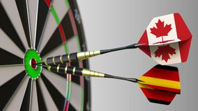 Flags of Canada and Germany on darts hitting bullseye of the target. International cooperation or competition conceptual. Flags of Canada and Germany on darts stock video