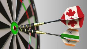 Flags of Canada and India on darts hitting bullseye of the target. International cooperation or competition conceptual. Flags of Canada and India on darts stock video footage
