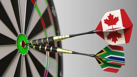 Flags of Canada and South Africa on darts hitting bullseye of the target. International cooperation or competition. Animation stock video