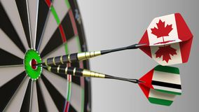 Flags of Canada and the UAE on darts hitting bullseye of the target. International cooperation or competition conceptual. Flags of Canada and the UAE on darts stock footage