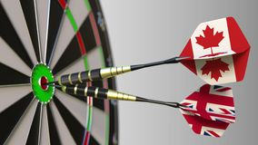 Flags of Canada and the United Kingdom on darts hitting bullseye of the target. International cooperation or competition. Animation stock video