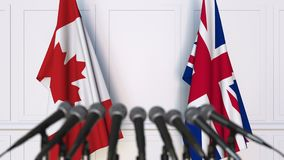 Flags of Canada and The United Kingdom at international meeting or negotiations press conference. 3D animation stock video