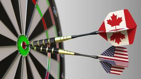Flags of Canada and the USA on darts hitting bullseye of the target. International cooperation or competition conceptual. Flags of Canada and the USA on darts stock footage