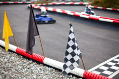Flags and cars on carting track Royalty Free Stock Photo