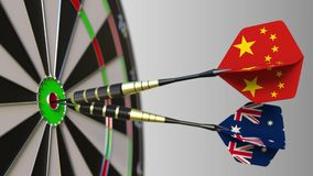 Flags of China and Australia on darts hitting bullseye of the target. International cooperation or competition. Animation stock video footage