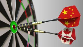 Flags of China and Canada on darts hitting bullseye of the target. International cooperation or competition conceptual. Flags of China and Canada on darts stock video