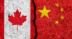 Flags of China and Canada painted on cracked grunge wall background/Canada and China relations and conflict concept royalty free stock photo