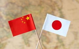 Flags of China and Japan over the world map, political relations concept image stock photography