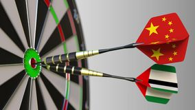 Flags of China and the UAE on darts hitting bullseye of the target. International cooperation or competition conceptual. Flags of China and the UAE on darts stock video footage