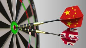 Flags of China and the United Kingdom on darts hitting bullseye of the target. International cooperation or competition. Animation stock video footage