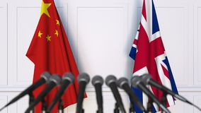 Flags of China and The United Kingdom at international meeting or negotiations press conference. 3D animation stock video