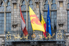 Flags on City Hall facade in Mons, Belgium. Flags waving on City Hall building facade in Mons, capital of the Wallonian province of Hainaut in Belgium Stock Image