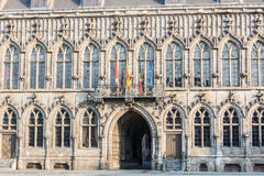 Flags on City Hall facade in Mons, Belgium. Flags waving on City Hall building facade in Mons, capital of the Wallonian province of Hainaut in Belgium Royalty Free Stock Images