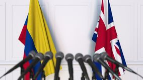 Flags of Colombia and The United Kingdom at international meeting or negotiations press conference. 3D animation stock footage