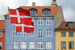 Flags and colored houses in Copenhagen, Denmark. Copenhagen view with flags of Denmark over the typical danish colorful houses Stock Photo