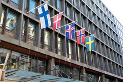 The flags of the countries of Scandinavia waving on hotel building in Helsinki of a beautiful summer day. royalty free stock image