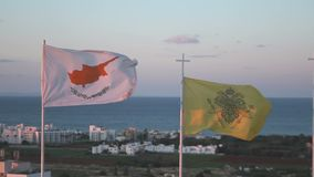 Flags of Cyprus and Greek Orthodox Church waving in wind, seascape on background. Stock footage stock video