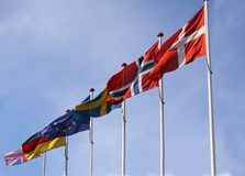 Flags from Denmark, Norway, Sweden, Germany and United Kingdom waving from flagpoles together with the EU, European Union, flag ag. Ainst a blue sky - stock royalty free stock image
