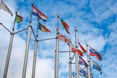 Flags of different countries on blue sky background Royalty Free Stock Images