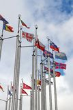 Flags of different countries on cloudy sky background Stock Image