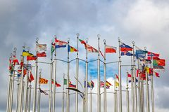 Flags of different countries on cloudy sky background Royalty Free Stock Image