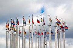 Flags of different countries on cloudy sky background Royalty Free Stock Photo